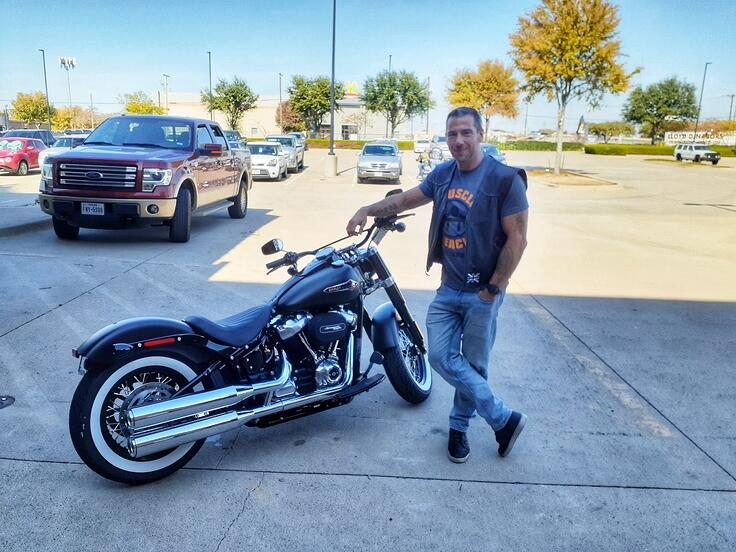 Steve Micklewright posing with his Harley Davidson motorcycle
